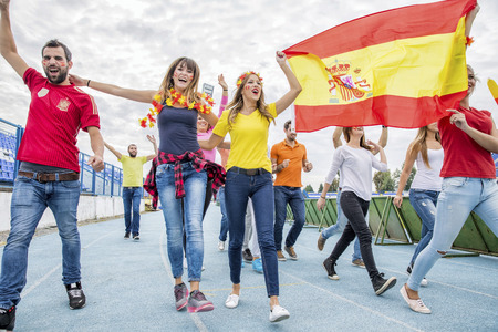 cheer full: Group of soccer fans celebrating with Spanish flag