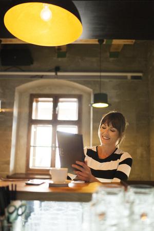 Woman in coffee shop using digital tablet LANG_EVOIMAGES