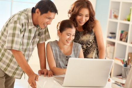 asian teenager: Proud parents looking at what their daughter is showing to them on her laptop. Stock Photo