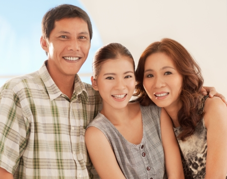 A happy Asian family smiling and posing for photographing. Stock Photo