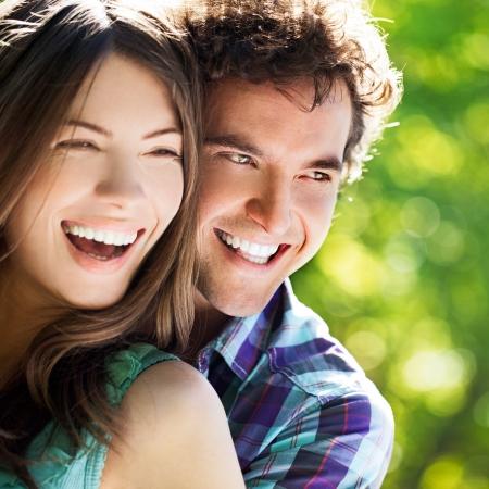 s úsměvem: Mladý šťastný pár objímání a smál se.
