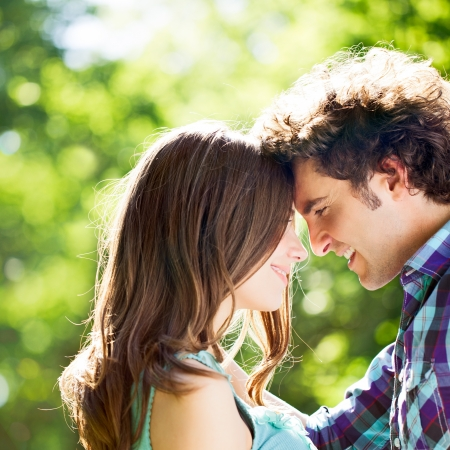 forehead: A happy couple standing face to face and smiling. Stock Photo
