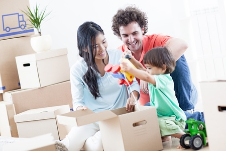 home moving: Young happy family relaxing after they have moved into their new home.