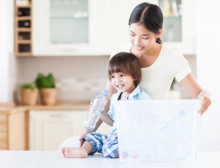 niños reciclando: Una madre cariñosa que enseña a su hijo acerca de la importancia del reciclaje. Foto de archivo