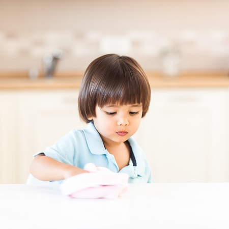 A cute little boy cleaning the counter top in the kitchen. photo