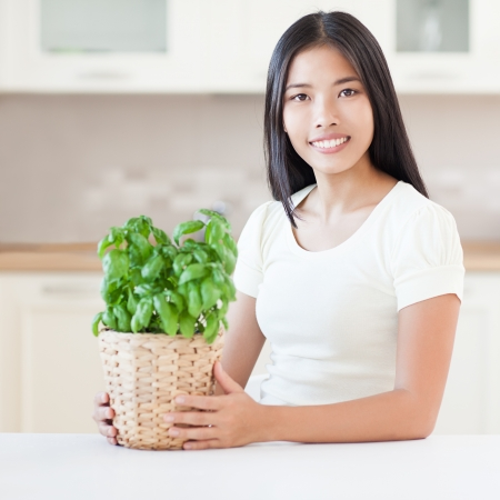 indoor plants: Young Asian woman with a plant shes growing in her kitchen.