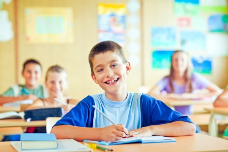 school age boy: A cute schoolboy sitting in his classroom with his classmates. Stock Photo