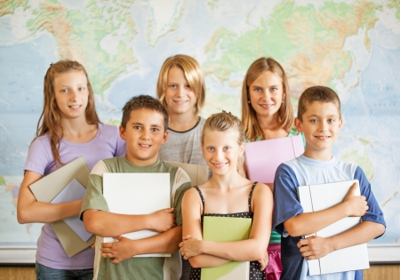 elementary age girl: A group of elementary students posing on front of a world map.