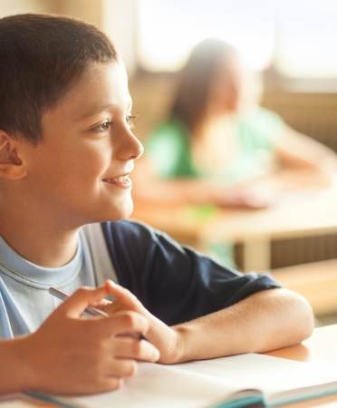 10 11 years: A boy sitting at his desk at school. Stock Photo