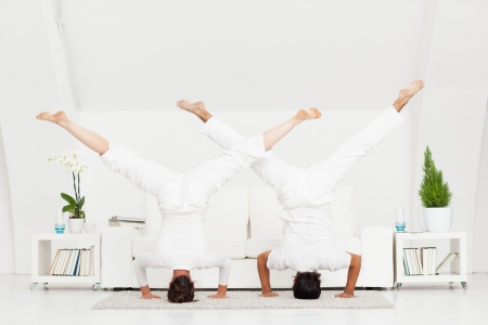 headstand: Young couple doing a headstand at home.