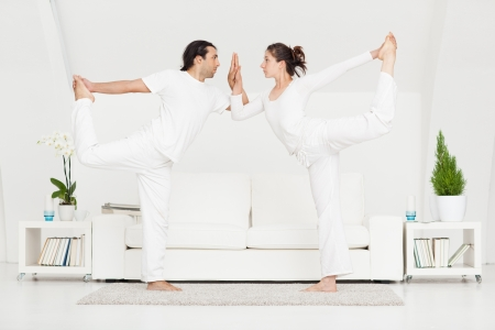 zen interior: Young Caucasian couple doing yoga at home.