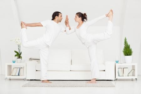 zen interior: Young Caucasian couple doing yoga at home.