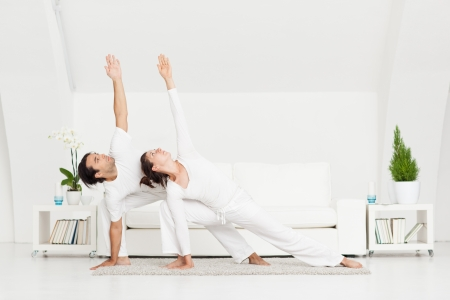 Young couple in the Extended Side Angle yoga position. photo