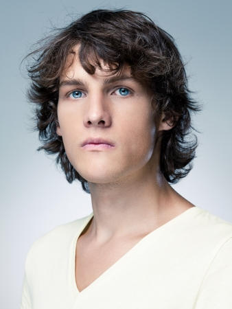 brown hair blue eyes: Portrait of a serious blue-eyed young man in front of a blue background. Stock Photo