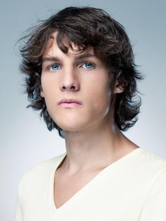 hombres jovenes: Retrato de un hombre joven de ojos azules seria delante de un fondo azul.
