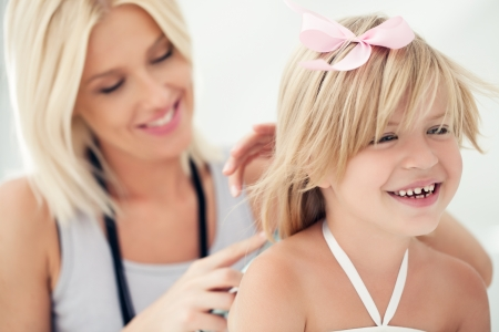 combing hair: Mid-adult mother combing her cute daughters hair.