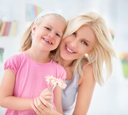 A cute girl posing with her mother and holding a flower for her. photo