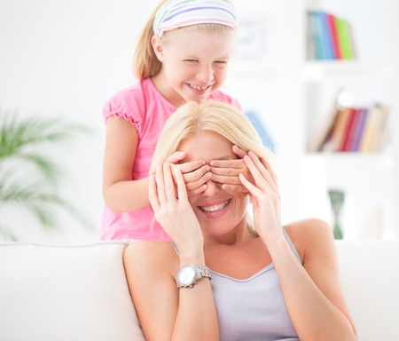 holding the head: A cute girl covering her mothers eyes so as to surprise her.