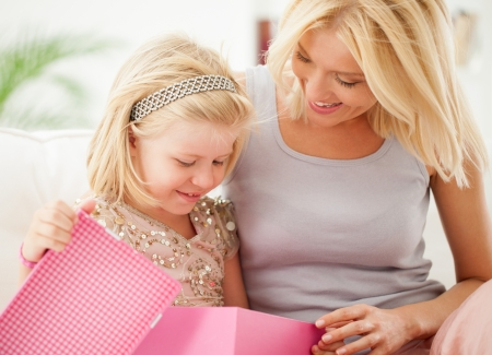 Mother and her daughter opening the little girl's birthday present. photo
