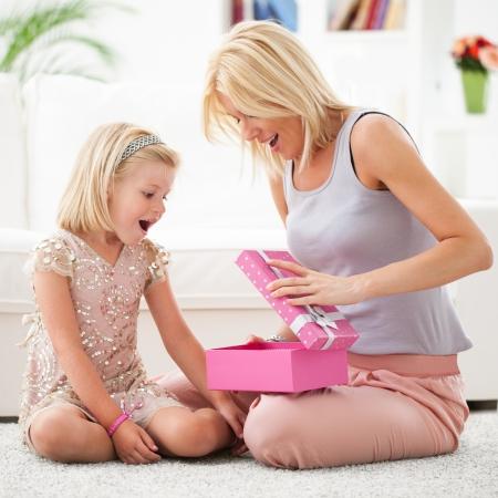 er�ffnung: Mutter und ihre Tochter die Er�ffnung eines rosa Geburtstagsgeschenk.