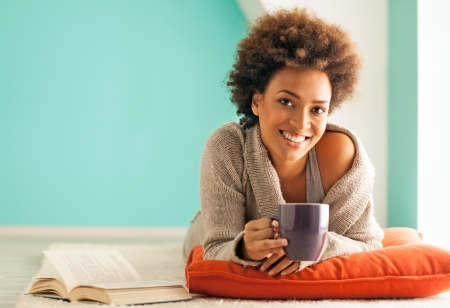 women coffee: Beautiful young African woman enjoying a cup of coffee while relaxing at home.