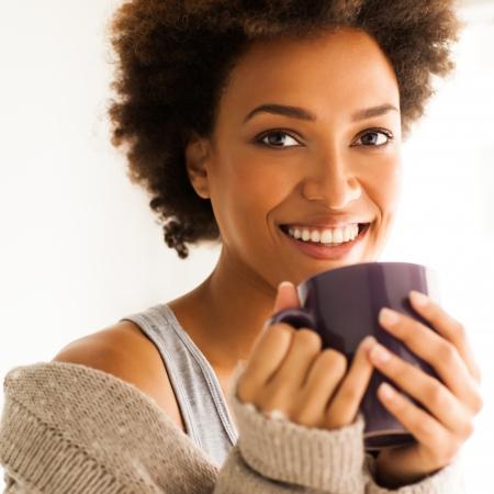femme africaine: Belle jeune femme africaine en dégustant une tasse de café.