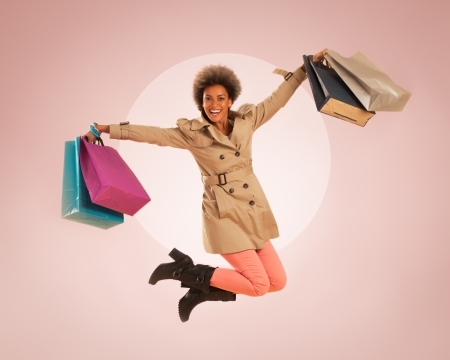 shoulder bag: Young African woman jumping with shopping bags in her hands. Stock Photo