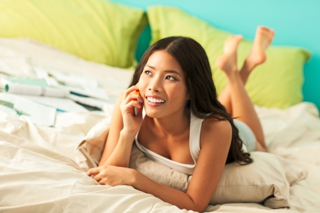 call girl: Smiling Asian teenage girl lying on her bed and making a phone call.
