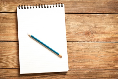 Blank notepad and a blue pencil on a wooden surface. Stock Photo - 19098973