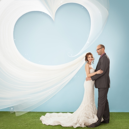 beautiful bride: Groom and bride whose veil is in the air forming a heart shape.