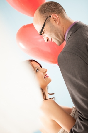 Smiling bride and groom looking at each other and holding heart-shaped balloons. photo