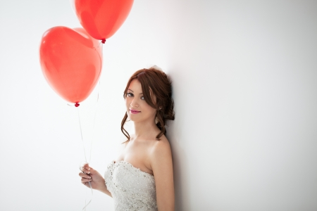 Beautiful young bride standing against the wall and holding heart-shaped balloons. photo
