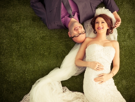 Smiling bride and groom lying on the grass-like carpet. photo