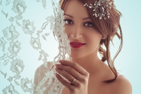 studio photography: Portrait of a beautiful bride smiling behind her veil.