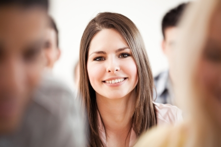 Smiling college student sitting surrounded by her friends. Stock Photo - 19563078