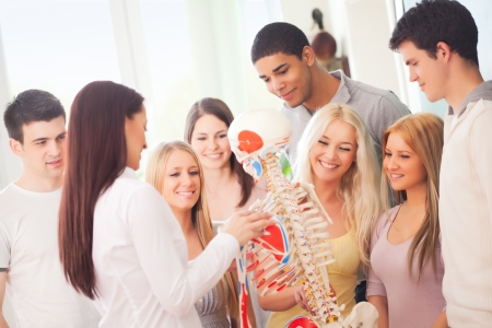 bone anatomy: Anatomy teacher and her students during a lesson.