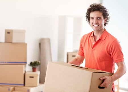 A handsome man holding a cardboard box while moving into a new apartment. photo