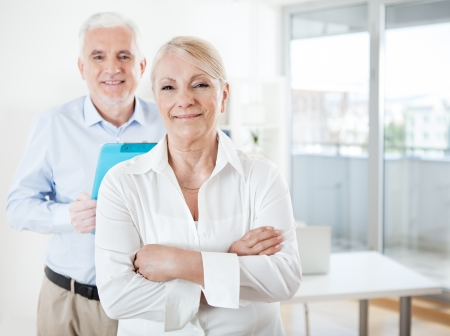 old office: Senior businessman and a businesswoman  smiling and posing in their office.