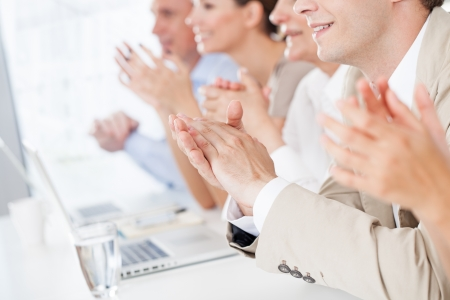 people clapping: Group of business people applauding in a meeting.