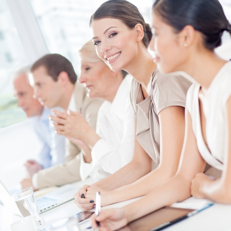 Smiling businesswoman sitting in a meeting with her colleagues. Stock Photo