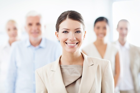 Smiling businesswoman standing in front of her business team.