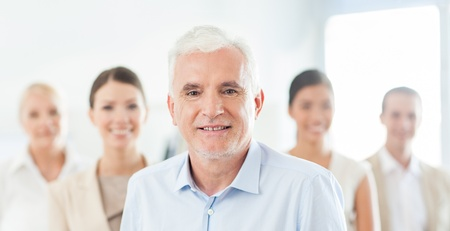 five people: Smiling senior businessman in front of his business team. Stock Photo