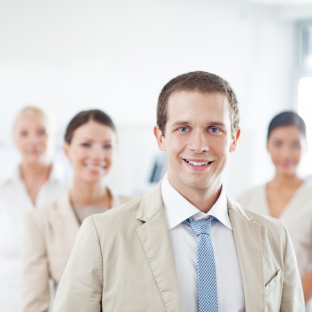 Smiling young businessman standing in front of his business team. photo