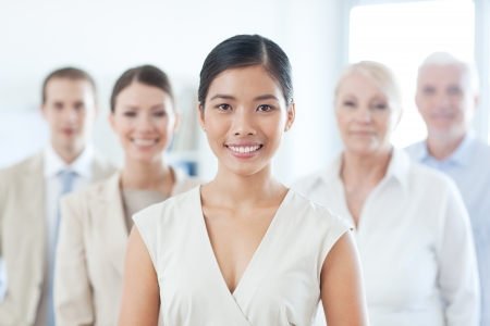 european people: Smiling Asian businesswoman standing in front of her business team. Stock Photo
