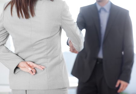 Business partners shaking hands with one of them holding her fingers crossed behind her back. photo