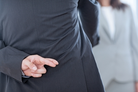 hope indoors luck: Business partners shaking hands with one of them holding her fingers crossed behind her back. Stock Photo