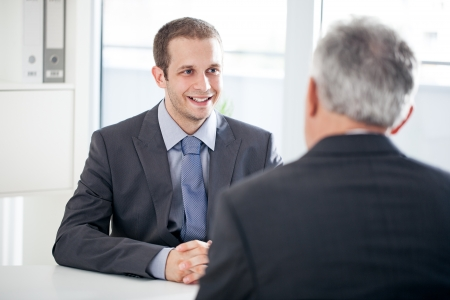 two people talking: A candidate for a job talking to the interviewer.