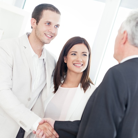 A married couple shaking hands with their financial advisor.