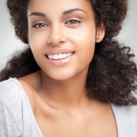 femme africaine: Belle femme souriante africaine posant sur un fond gris. Banque d'images