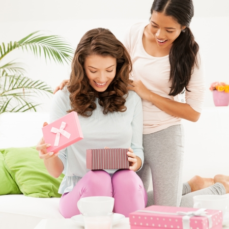 gift giving: Two friends sharing the happy moments of opening a birthday present  Stock Photo